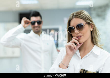 8ee23838fbeeed ... Couple d essayer sur des lunettes de soleil dans les lunettes optiques  store Banque D