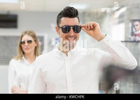 45befd986cb045 Couple d essayer sur des lunettes de soleil dans les lunettes optiques  store Banque D