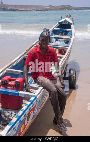 Jeune pêcheur assis dans un bateau de pêche sur la plage de Yoff, à Dakar, Sénégal Banque D'Images