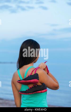 Vue arrière du thoughtful woman holding chaussures de sport tout en se tenant à la plage Banque D'Images