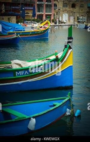Couleurs vives traditionnel maltais luzzu bateaux de pêche à St Julian's Bay, Malte, mer Méditerranée, Europe Banque D'Images