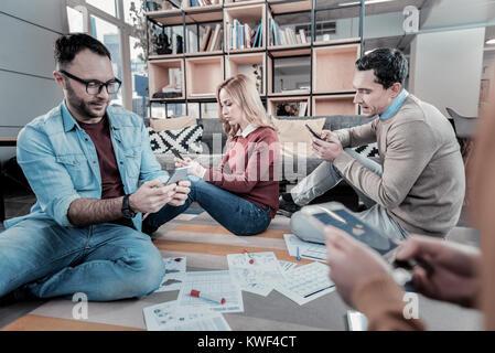 De graves et occupé. Smart concentrés employés occupés assise sur le sol autour des publications à l'aide de leurs Banque D'Images