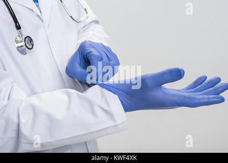 Préparation à la chirurgie. Close up of professionnel hommes de mains dans le processus de mettre des gants en latex Banque D'Images