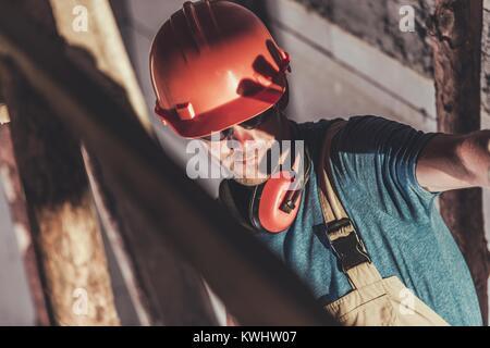 Soudage industriel inquiétant de la lumière. Site de construction couvrant les travailleurs de race blanche sa face de dangereux pour les yeux lumineux du voyant d'Électrique Nous