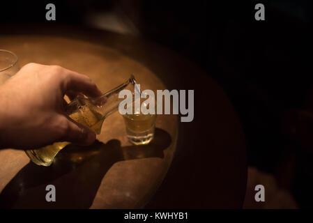 Remplir un cliché avec rakomelo grec traditionnel raki (avec du miel) dans une table en bois avec des conditions de faible luminosité