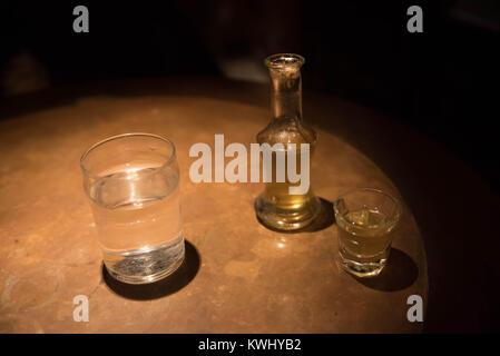 Un cliché et une bouteille remplie d'rakomelo grec traditionnel raki (avec du miel) à côté d'un verre d'eau dans une table en bois avec des conditions de faible luminosité