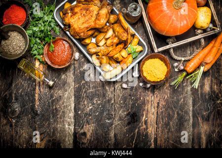 Poulet frit avec légumes et épices. Sur un fond de bois. Banque D'Images