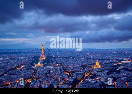 Vue aérienne de toits de Paris et les monuments illuminés (Tour Eiffel et Les Invalides) au crépuscule. 16e et 7e Banque D'Images