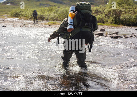 Randonneur marchant dans river Banque D'Images
