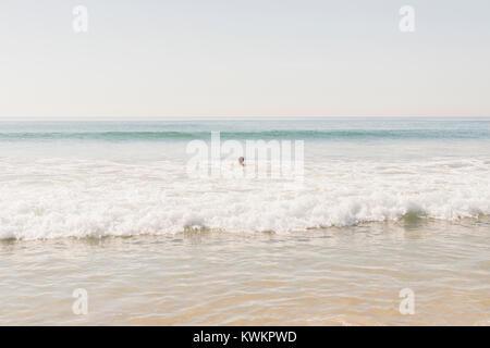 Vue de moyenne distance en natation garçon contre la mer ciel clair Banque D'Images