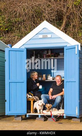 Bournemouth, Dorset, UK. 4 janvier, 2018. Météo France: Jour de vent à Bournemouth. Couple avec leurs chiens s'abriter Banque D'Images