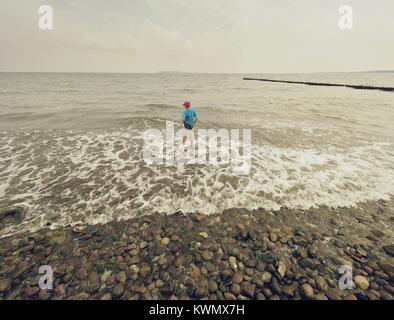 Garçon aux cheveux blonds séjour en mer froide Tide. Gosse sur plage de galets avec des vagues écumeuses. Jour venteux, Banque D'Images