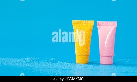 Abstract colorful tubes cosmétiques dans des gouttelettes d'eau. Médecine hygiène rafraîchissante, fournitures de Banque D'Images