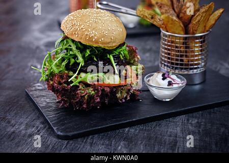 Burger, frites avec salade sur une table. Banque D'Images