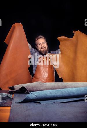 Travailleur du cuir professionnel découpe cuir à la tanner shop Banque D'Images
