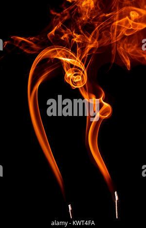 Image conceptuelle de sentiers de la fumée d'encens orange faire des formes d'intérêt. Banque D'Images