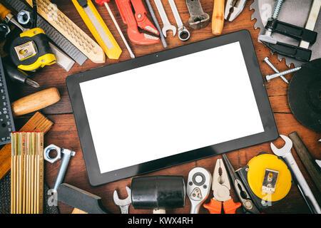 Variété d'outils à main et comprimé sur une table en bois Banque D'Images