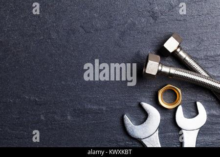Concept plomberie tuyaux et outils. sur une ardoise foncé bakground Banque D'Images