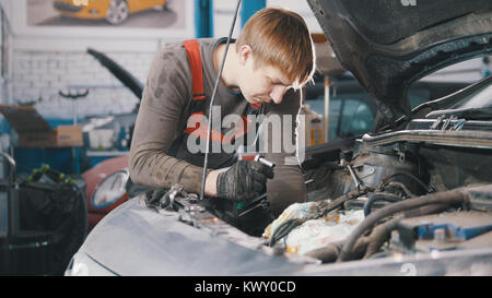 La vérification et la réparation mécanique moteur automobile, la réparation de voiture, travaillant dans l'atelier, Banque D'Images
