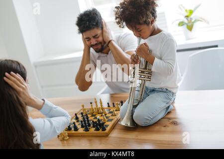 La mère et le père essayant de jouer aux échecs pendant que leur enfant joue trompette
