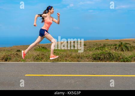 Vue latérale photo de jeune joueur professionnel coureuse sur route - course de vitesse personnelle de formation Banque D'Images