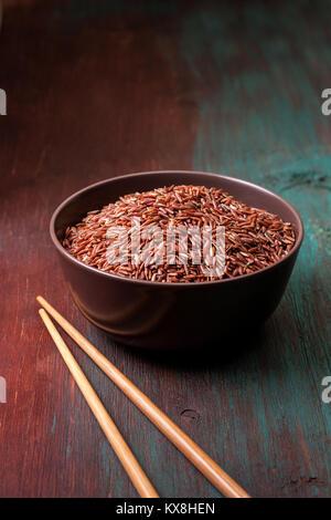 Riz rouge dans un bol en céramique sur le vieux fond de bois Banque D'Images
