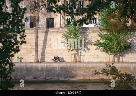 Les jeunes Paris, vue d'un couple sous le soleil le long du quai d'Orléans sur l'Ile Saint Louis au centre de Paris, Banque D'Images