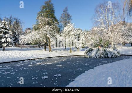 Canard étang gelé à Grove Park, Harborne, Birmingham sur une journée d'hiver ensoleillée après de fortes chutes de neige.