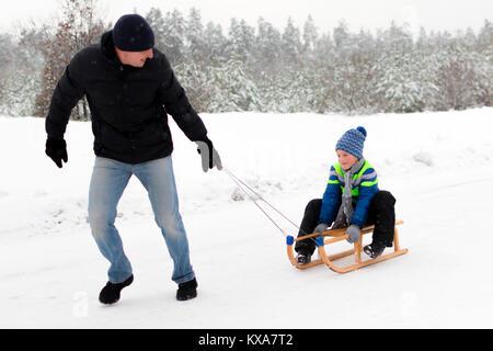 Jeune père et fils à la luge hiver Banque D'Images