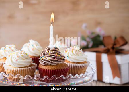De délicieux petits gâteaux d'anniversaire avec une bougie servi sur du verre sur table en bois fête cakestand Banque D'Images