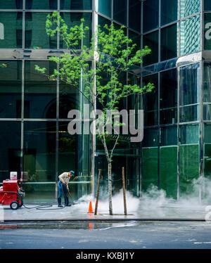 Mai 1982,New York,nettoyage travailleur trottoir avec tuyau d'eau haute pression,Park Avenue Plaza,52e Rue, Manhattan, Banque D'Images