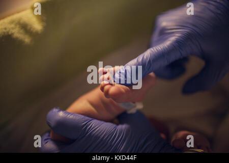 Les mains coupées de pédiatre de toucher le pied de bébé nouveau-né à l'hôpital