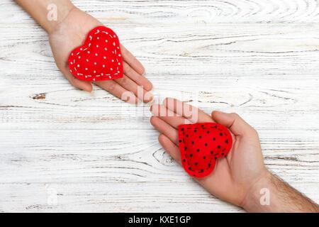 Love Concept: Girl holding et coeur rouge de donner à son petit ami part isolé sur fond blanc. Banque D'Images