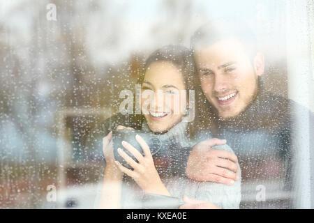 Vue avant, portrait d'un couple positif à l'extérieur par une fenêtre dans un jour pluvieux de l'hiver à la maison Banque D'Images
