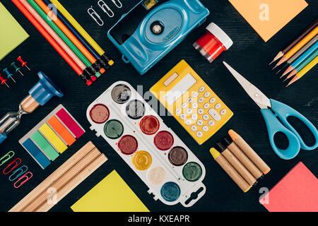 Mise à plat de la composition des fournitures scolaires colorées isolé sur fond foncé board