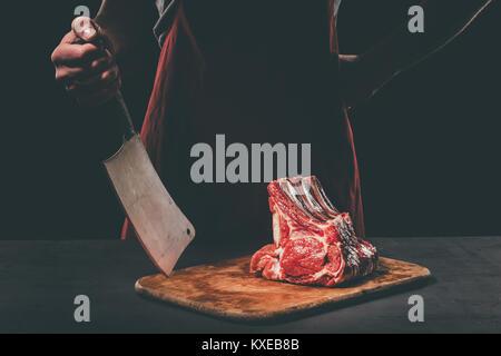 Butcher avec cleaver et la viande sur une planche à découper en bois Banque D'Images