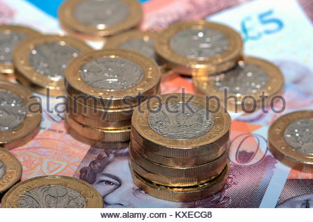 Pile d'une livre de monnaie et des billets de banque qui peuvent être utilisés pour payer des factures ou d'épargne Banque D'Images