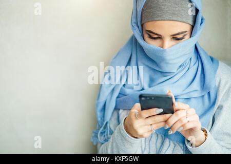 Jeune femme musulmane utiliser smart phone in cafe Banque D'Images