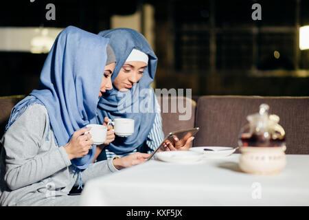 Jolie femme musulmane utiliser tablet in cafe Banque D'Images