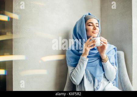 Jolie jeune fille musulmane en hijab in cafe Banque D'Images