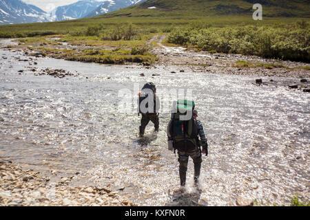 Vue arrière de randonneurs marchant dans river Banque D'Images