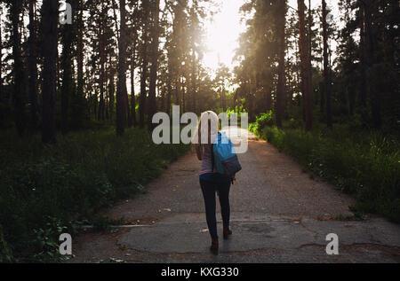 Vue arrière du sac à dos femme marche sur route de campagne au milieu d'arbres en forêt
