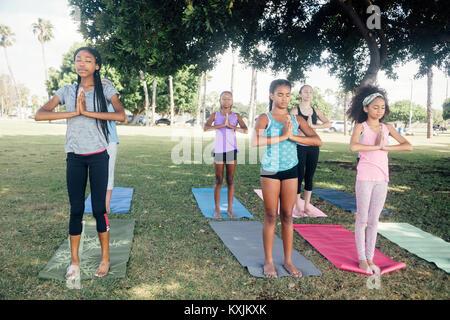 Les filles et les jeunes filles pratiquant le yoga de la posture de l'école sur le terrain de jeu Banque D'Images