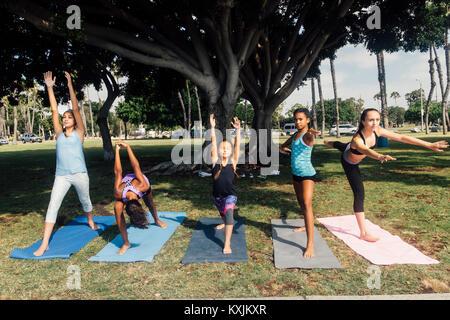 Les filles et les jeunes filles pratiquant le yoga warrior présentent pour l'école du jeu Banque D'Images