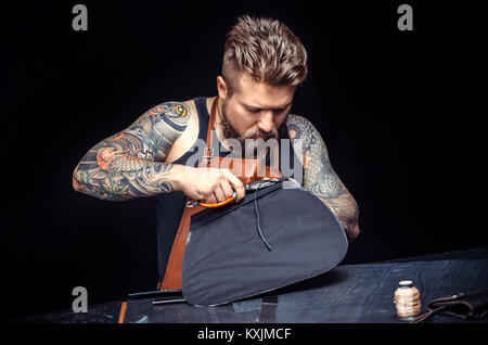 Travailleur du cuir professionnel découper des formes en cuir pour un nouveau produit dans sa zone de travail Banque D'Images
