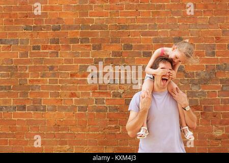 Fille se porter à l'épaule de père avec ses yeux couvrant par brick wall Banque D'Images