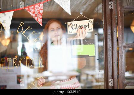 Propriétaire de petite entreprise en cafe tournant closed sign Banque D'Images
