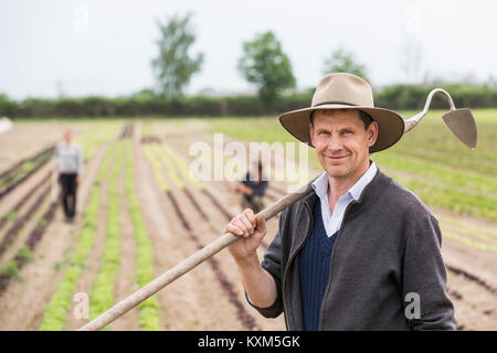 Portrait of farmer in field with hoe Banque D'Images