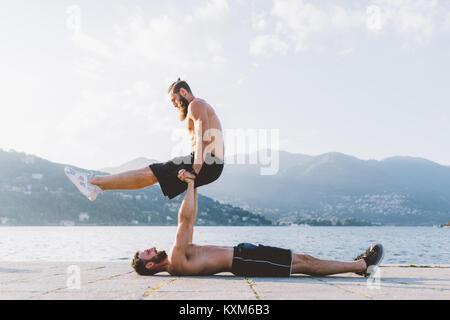 Jeune homme allongé sur le dos des ami sur le bord de lac de Côme, Lombardie, Italie, Banque D'Images