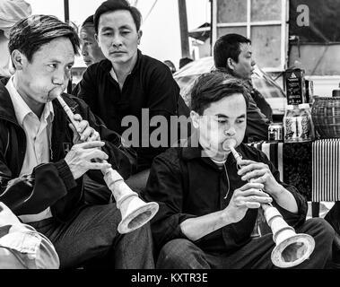 Les hommes à l'instrument de musique traditionnelle à Sapa marché, Vietnam Banque D'Images